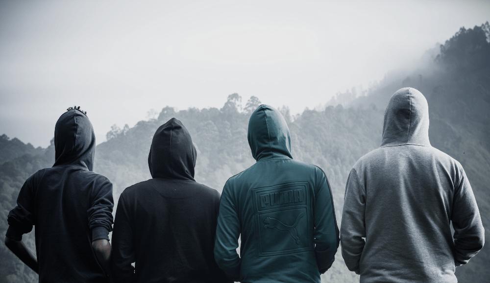 four men wearing hoodie sweatshirts