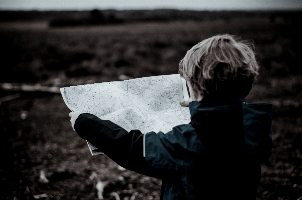 young child holding a map