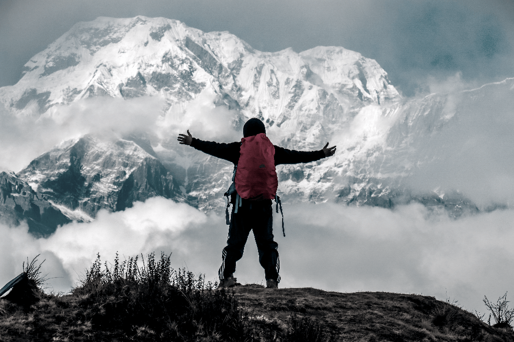 man standing on top of a mountain with arms out