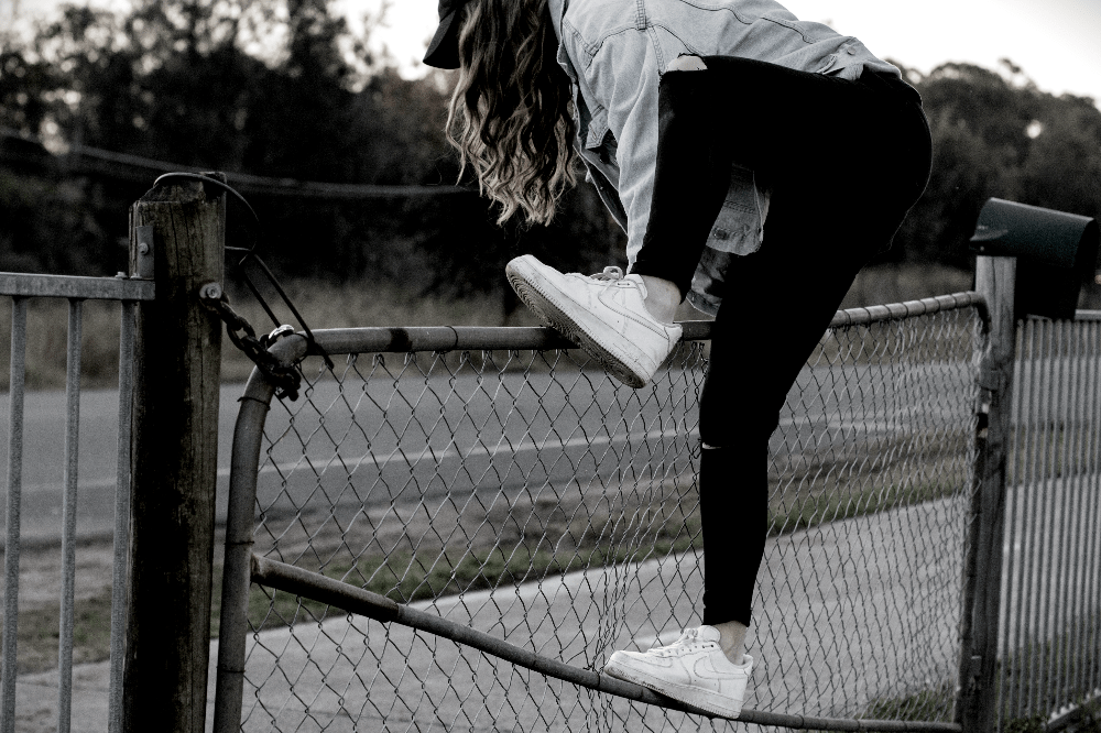 woman vaulting over a fence