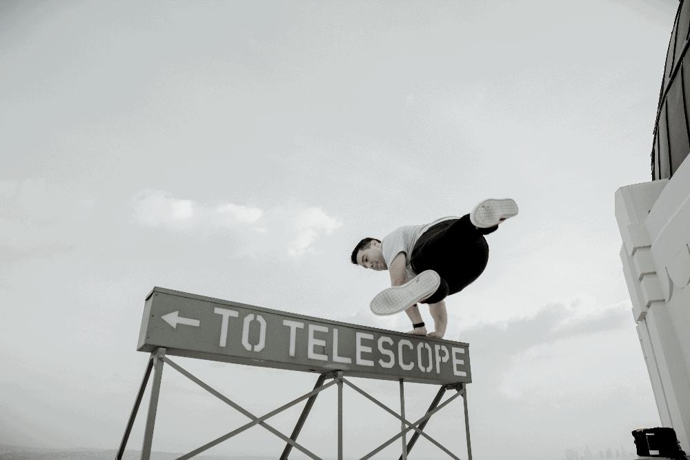 man vaulting over a sign